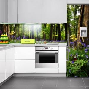 Piękny widok na zielony wiosenny las zdobi ścianę nad blatem (w postaci fototapety) i pokrywa fronty lodówki (jako naklejka dekoracyjna). Fot. Decomania