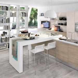Biblioteczka na granicy kuchni i salonu pełni rolę elementu działowego we wnętrzu. Półki na przestrzał przepuszczają światło. Fot. Cucine Lube