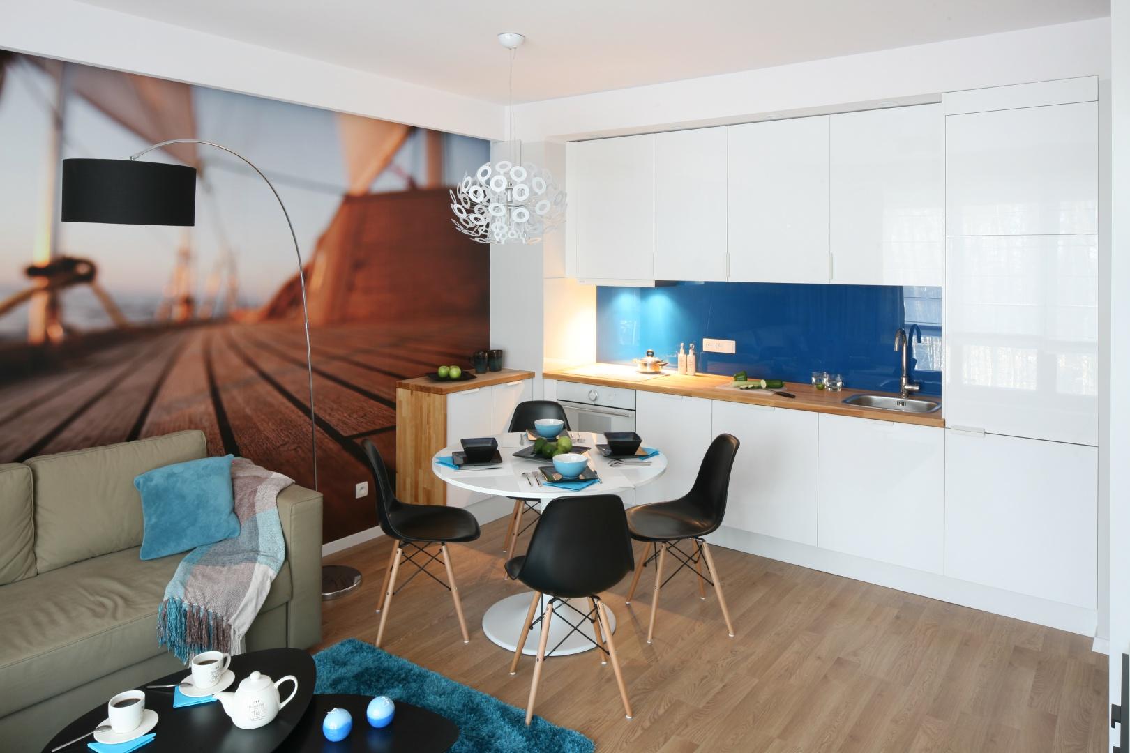 Aneks kuchenny z białą lakierowaną zabudową jest równie nowoczesny co salon; obie strefy łączy kolor niebieski. Projekt: Anna Maria Sokołowska. Fot. Bartosz Jarosz