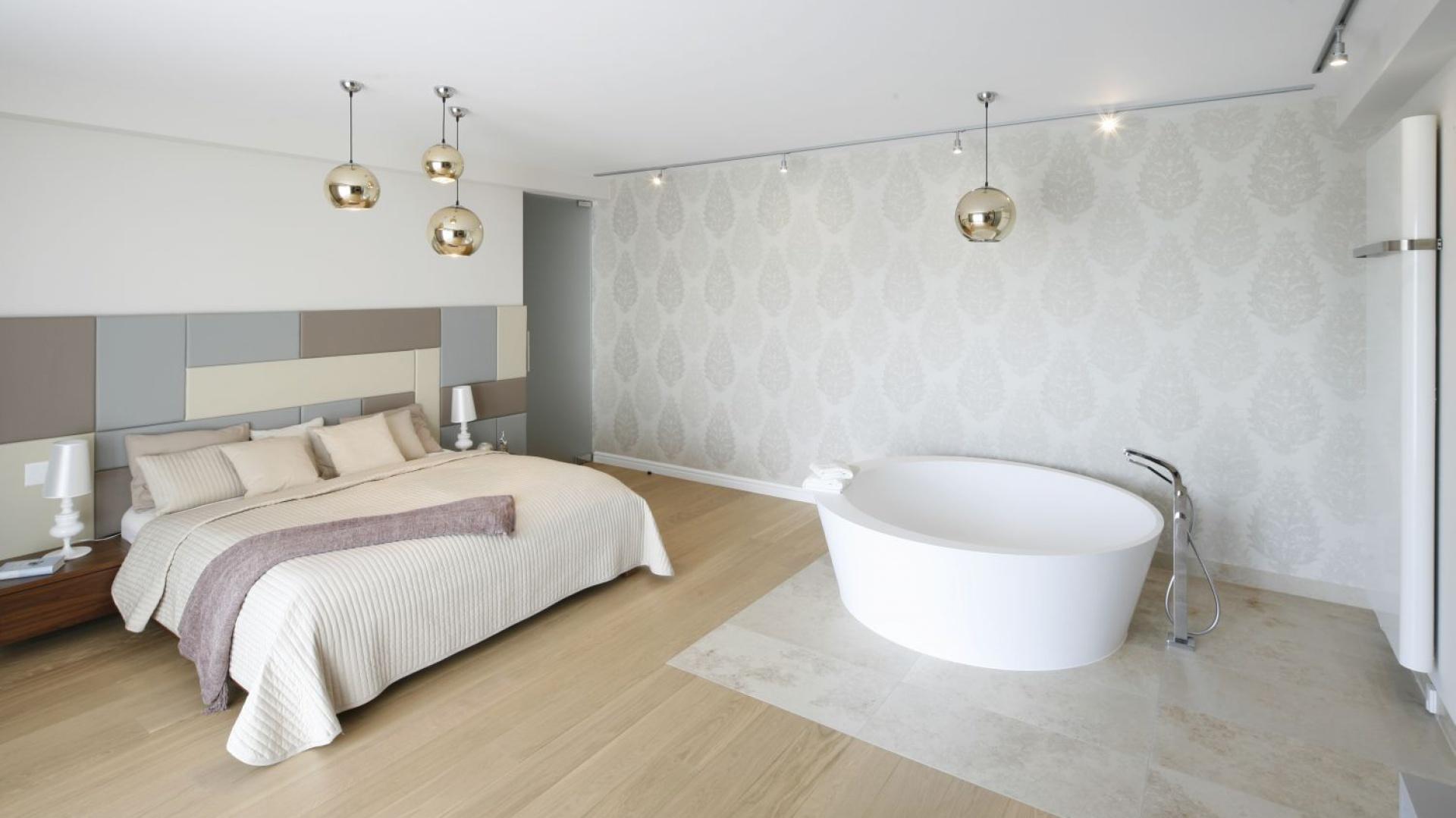 Sypialnię i strefę kąpieli urządzono na jednej przestrzeni. Podłogę, gdzie stoi wanna wolno stojąca wykończono inną okładziną. Projekt: Katarzyna Mikulska-Sękalska. Fot. Bartosz Jarosz