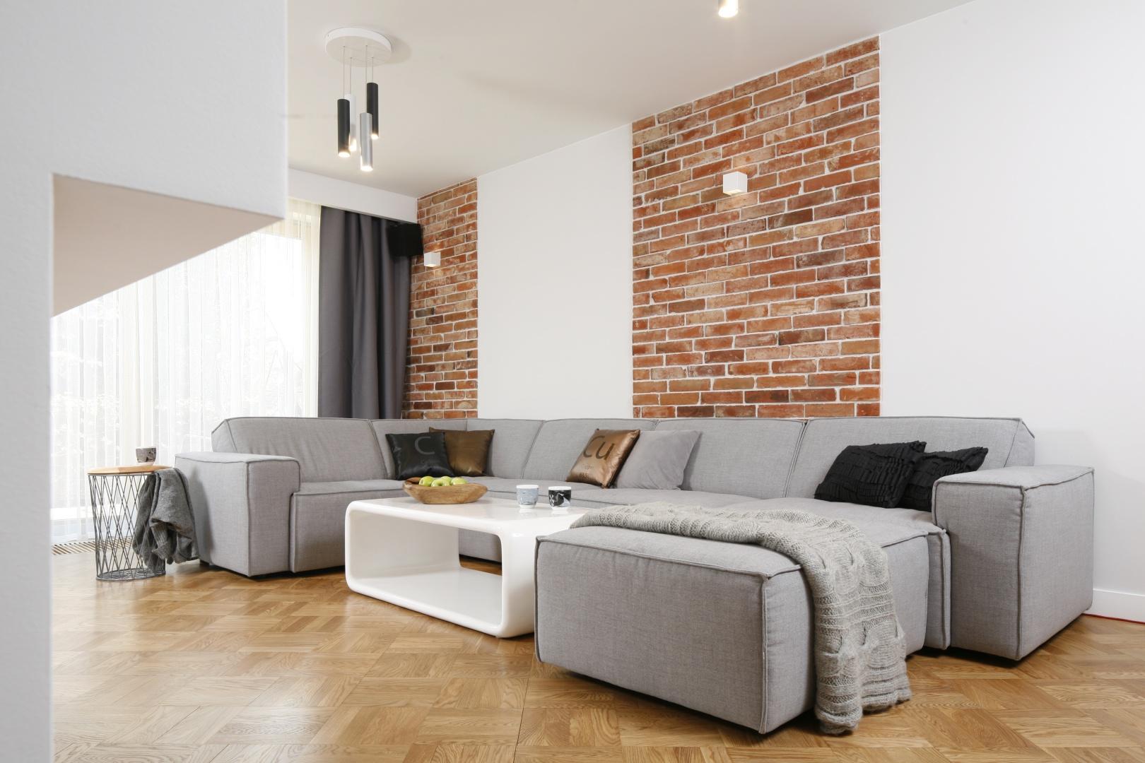 Szara kanapa narożna świetne prezentuje się  na tle ceglanej ściany w salonie urządzony w klimacie lot. Projekt: Agat Piltz. Fot. Bartosz Jarosz