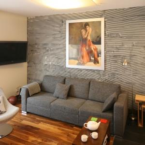 Niewielka szara kanapa stanowi wyposażenie strefy wypoczynku w małym salonie: świetnie prezentuje się na tle ściany wykończonej dekoracyjną fakturą. Projekt: Marcin Lewandowicz. Fot. Bartosz Jarosz