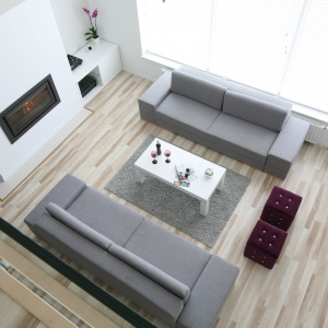 Dwie eleganckie szare kanapy organizują przestrzeń salonu o imponującej wysokości. Projekt: Karolina i Artur Urban. Fot. Bartosz Jarosz