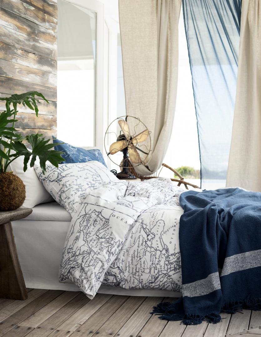 Przetarte drewno na podłodze i ścianie, do tego granatowo-biała pościel z kartograficznymi nadrukami. W tej sypialni króluje styl marynistyczny. Fot. H&M Home