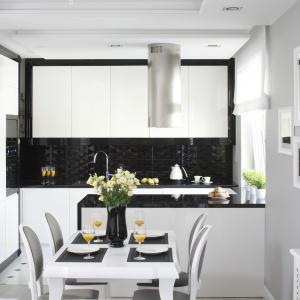 Urządzona w bieli i czerni kuchnia stanowi efektowne tło dla jadalni. Projekt: Katarzyna Mikulska-Sękalska. Fot. Bartosz Jarosz