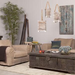 Stylizowany na stary kufer pełni rolę stolika kawowego. Na ścianach zawisły ciekawe dekoracje przedstawiające postarzane drewno. Fot. Inne Meble
