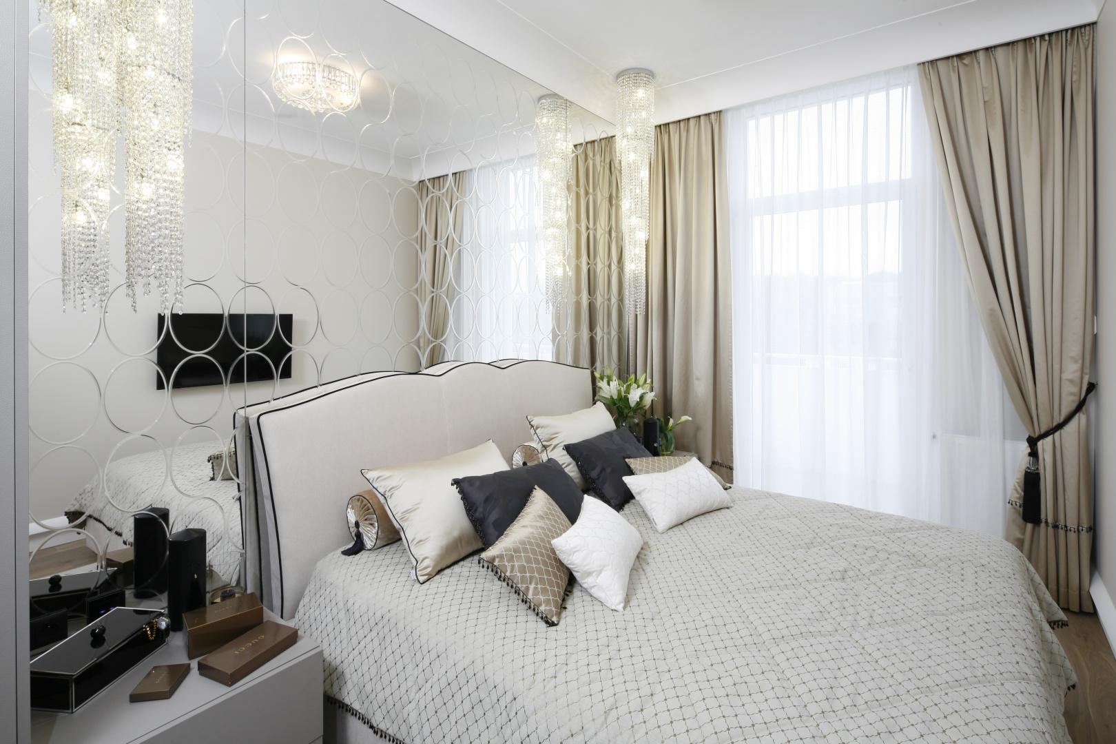 Sypialnię urządzono w jasnych odcieniach beżów, a wnętrze dodatkowo rozświetla oryginalne wykończenie ściany za łóżkiem w postaci dużej tafli lustrzanej z dekoracyjnymi ornamentami. Projekt: Karolina Łuczyńska. Fot. Bartosz Jarosz