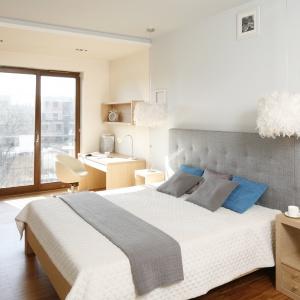 """Białe ściany i szary tapicerowany zagłówek zestawiono z jasnym odcieniem drewna, które ociepla aranżację tej sypialni. Całość dopełniają białe """"kosmate"""" lampy. Projekt: Marta Kruk. Fot. Bartosz Jarosz"""