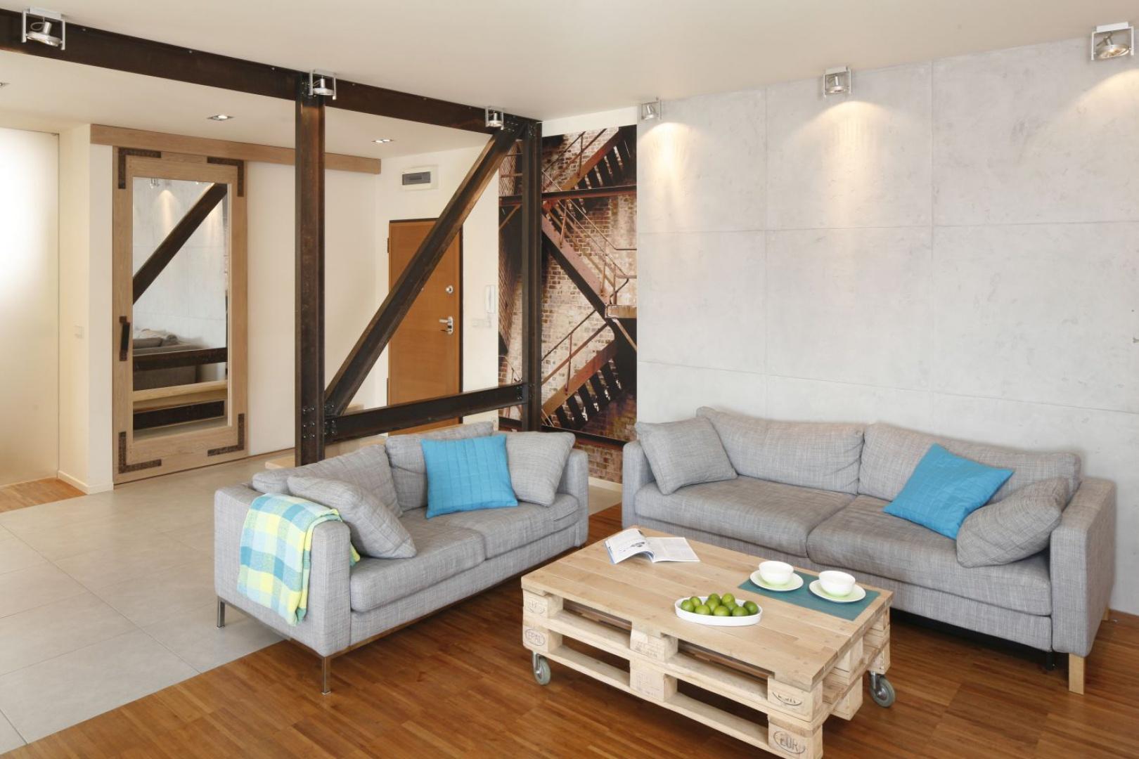Salon w stylu loft swój charakter zyskał dzięki metalowym belkom, betonowi na ścianie oraz