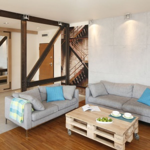 """Salon w stylu loft swój charakter zyskał dzięki metalowym belkom, betonowi na ścianie oraz """"fabrycznej"""" fototapecie w holu. Projekt: Marta Kruk. Fot. Bartosz Jarosz"""
