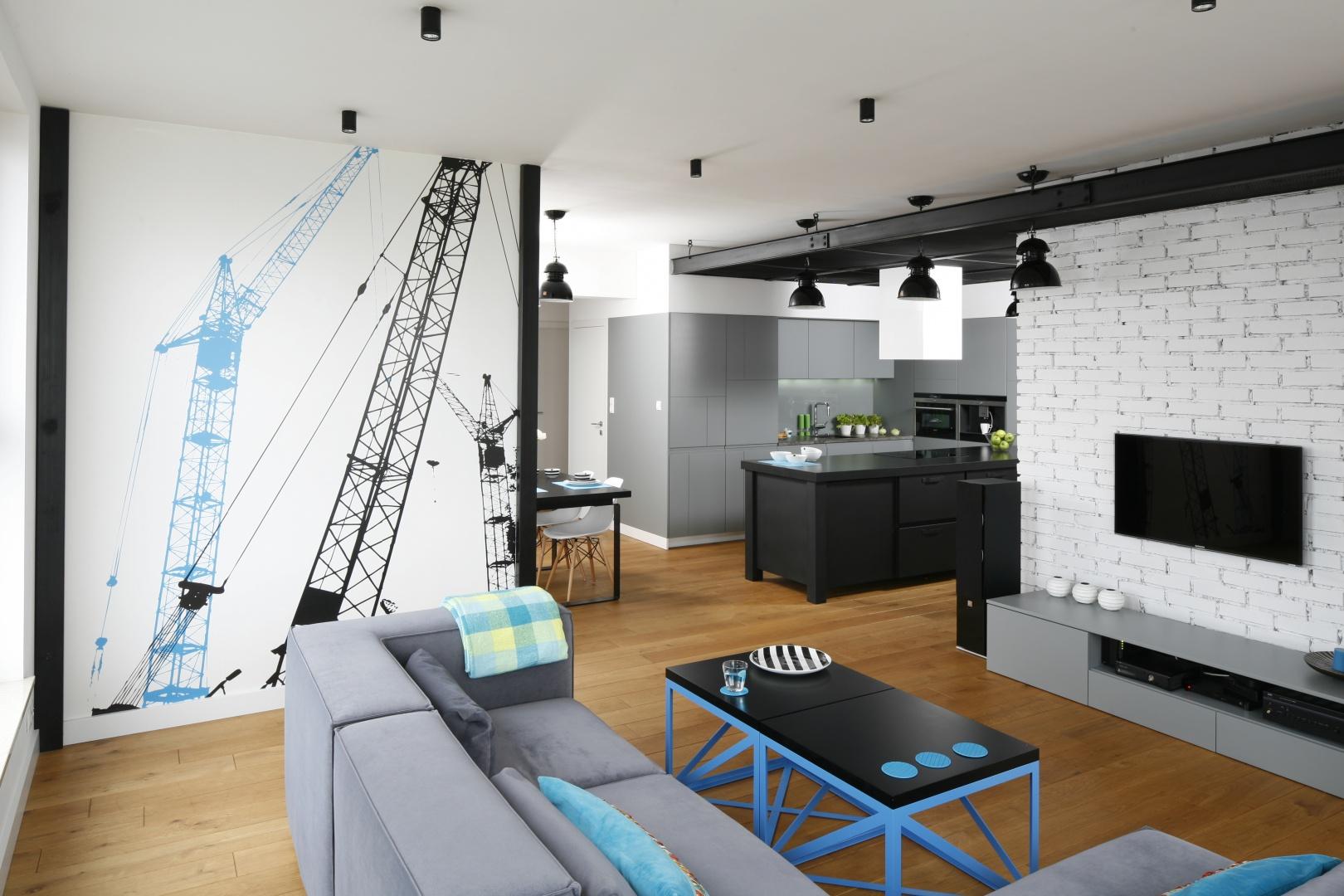 Salon połączony z kuchnią urządzono w klimacie loftowym. Industrialny efekt zyskano dzięki białej cegle na ścianie za TV,