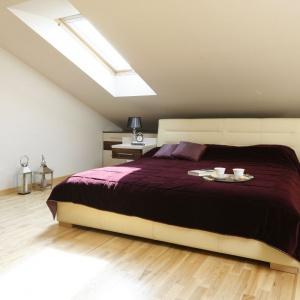 Urządzona na poddaszu sypialnia zyskuje wrażenie większej przestrzeni za sprawą jasnych ścian i jasnego drewna na podłodze. Projekt: Jolanta Kwilman. Fot. Bartosz Jarosz