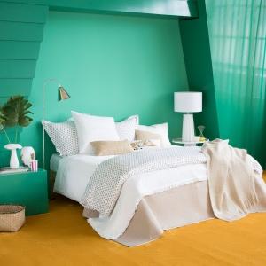 Łóżko z jasną pościelą stanęło na tle soczyście zielonej ściany. Fot. Zara Home