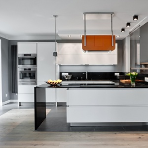 Oktawia listwowy to model kuchni o pięknych gładkich białych frontach i cienkim, eleganckim czarnym blatem. Fot. Atlas Kuchnie