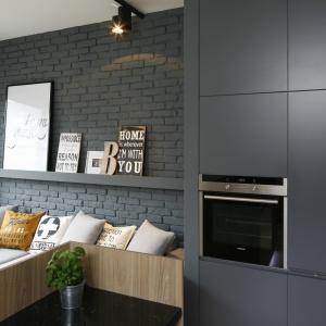Pomalowana na grafitowy odcień cegła, jasna, drewniana podłoga, biel i szarości zabarwione kolorem żółtym to kompozycja, która nie tylko idealnie oddaje loftowy klimat wnętrza, ale także gwarantuje spójność aranżacji.
