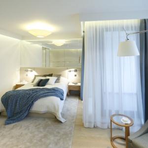 Lustro nad łóżkiem optycznie powiększa wnętrze. Projekt: Anna Fodemska. Fot. Bartosz Jarosz