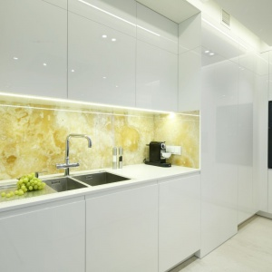 Ścianę nad blatem również wykończono naturalnym materiałem. Tym razem jest to szlachetny onyks. Projekt: Anna Fodemska. Fot. Bartosz Jarosz