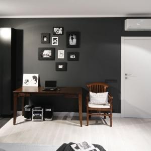 Sypialnia w czerni, którą zrównoważyło jasne drewno na podłodze i białe drzwi. Projekt: Maciejka Peszyńska-Drews. Fot. Bartosz Jarosz