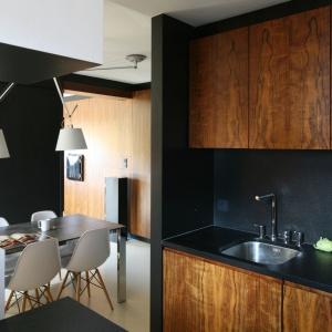 Przełamanie czerni kolorami drewna to świetny sposób na ożywienie aranżacji wnętrza. Projekt: Michał i Kasia Dudko. Fot. Bartosz Jarosz