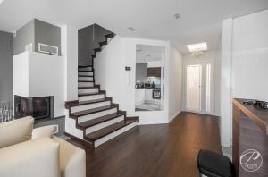 Usytuowane w salonie schody są oryginalnym elementem wystroju wnętrza. Niebanalna forma nadaje wnętrzu szczególnego charakteru.