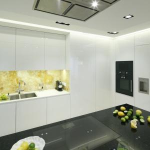 Ścianę nad blatem wykonano ze szlachetnego onyksu o żółtym odcieniu. Projekt: Anna Fodemska. Fot. Bartosz Jarosz