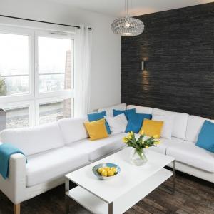 Biały wypoczynek na tle czarnej, łupkowej ściany ożywił zestaw poduszek, w tym błękitne i żółte. Projekt: Katarzyna Uszok. Fot. Bartosz Jarosz