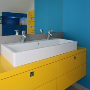 Łazienkę urządzono w letniej palecie barw. Żółtej szafce i grzejnikowi towarzyszą niebieskie ściany. Projekt: Małgorzata Galewska. Fot. Bartosz Jarosz