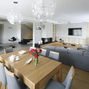 Przestronny elegancki salon połączono z jadalnią. Szarości zestawiono z dekorem jasnego drewna. Projekt: Katarzyna Mikulsaka-Sękalska. Fot. Bartosz Jarosz