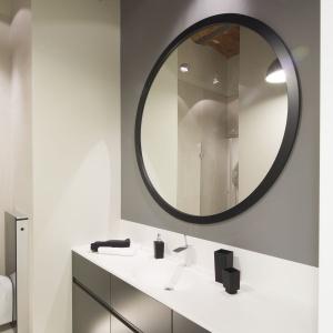W łazience nad szafką z umywalką zawisło okrągłe, nowoczesne lustro. Projekt: Szymon Chudy. Fot. Bartosz Jarosz