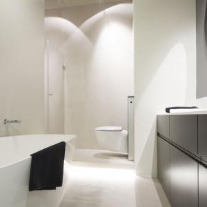 Łazienka została podzielona na dwie strefy: kąpielową i prysznica. Szafki oraz duże okrągłe lustro zostały wykonane na zamówienie. Projekt: Szymon Chudy. Fot. Bartosz Jarosz