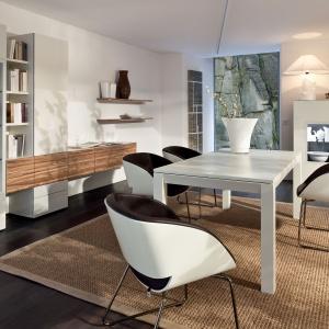Modułowy zestaw Neo Hülsta to propozycja do nowoczesnych wnętrz. Dostępny w wykończeniach: biały, szary, kakaowy, w połysku lub w macie. Lakierowane fronty ocieplono dębowym dekorem.  Krzesła wyróżniają się finezyjnym wyglądem. Ok. 19.500 zł (stół 160 cm). Fot. Hülsta