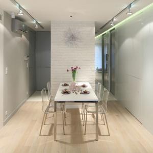 Za sprawą białej cegły na niewielkiej ściance, przy której stoi mały stół jadalniany, zaznaczono obecność jadalni. Projekt: Monika i Adam Bronikowscy. Fot. Bartosz Jarosz
