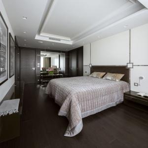 Każde pomieszczenie, bez względu na funkcje, zachowuje ten sam dystyngowany wygląd. Ściana za łóżkiem udekorowana została za pomocą stalowych profili, to kolejne odniesienie do stylu art déco. Fot. Yassen Hristov
