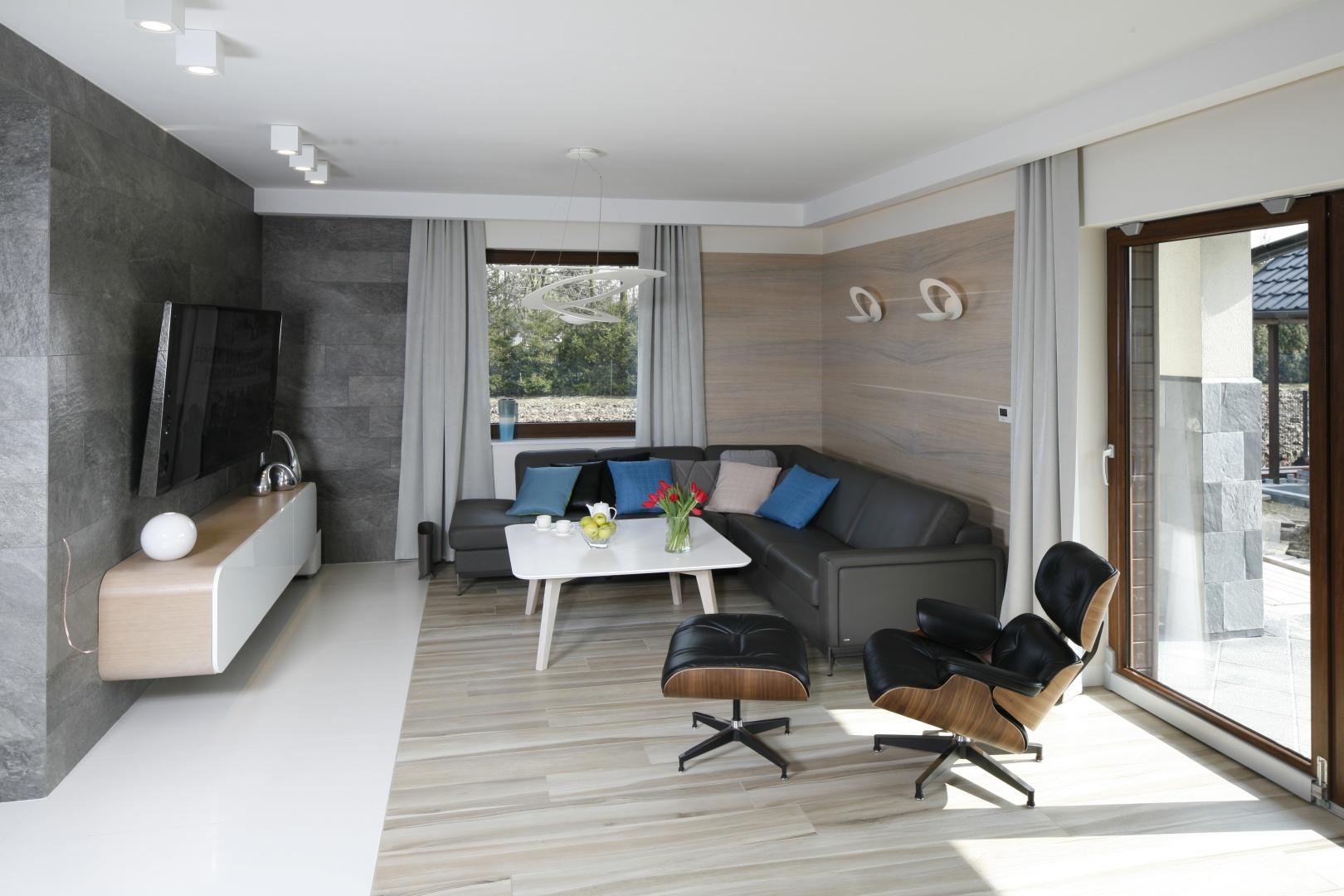 Na przeciw wielkoformatowego telewizora ustawiono narożnik oraz wygodny fotel z podnóżkiem. Projekt: Marta Kilan. Fot. Bartosz Jarosz