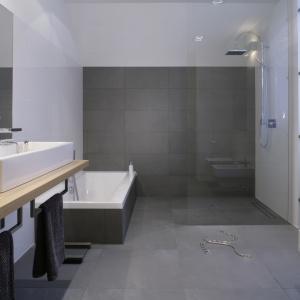 Prysznic w narożniku łazienki ma formę otwartą: szklana ścianka oddziela tę strefę od reszty łazienki. Proj. Michał Mikołajczak. Fot. Bartosz Jarosz