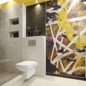 Abstrakcyjna barwna grafika z twarzą kobiety jest kolorowym akcentem w tej łazience. Projekt: Monika Olejnik. Fot. Bartosz Jarosz