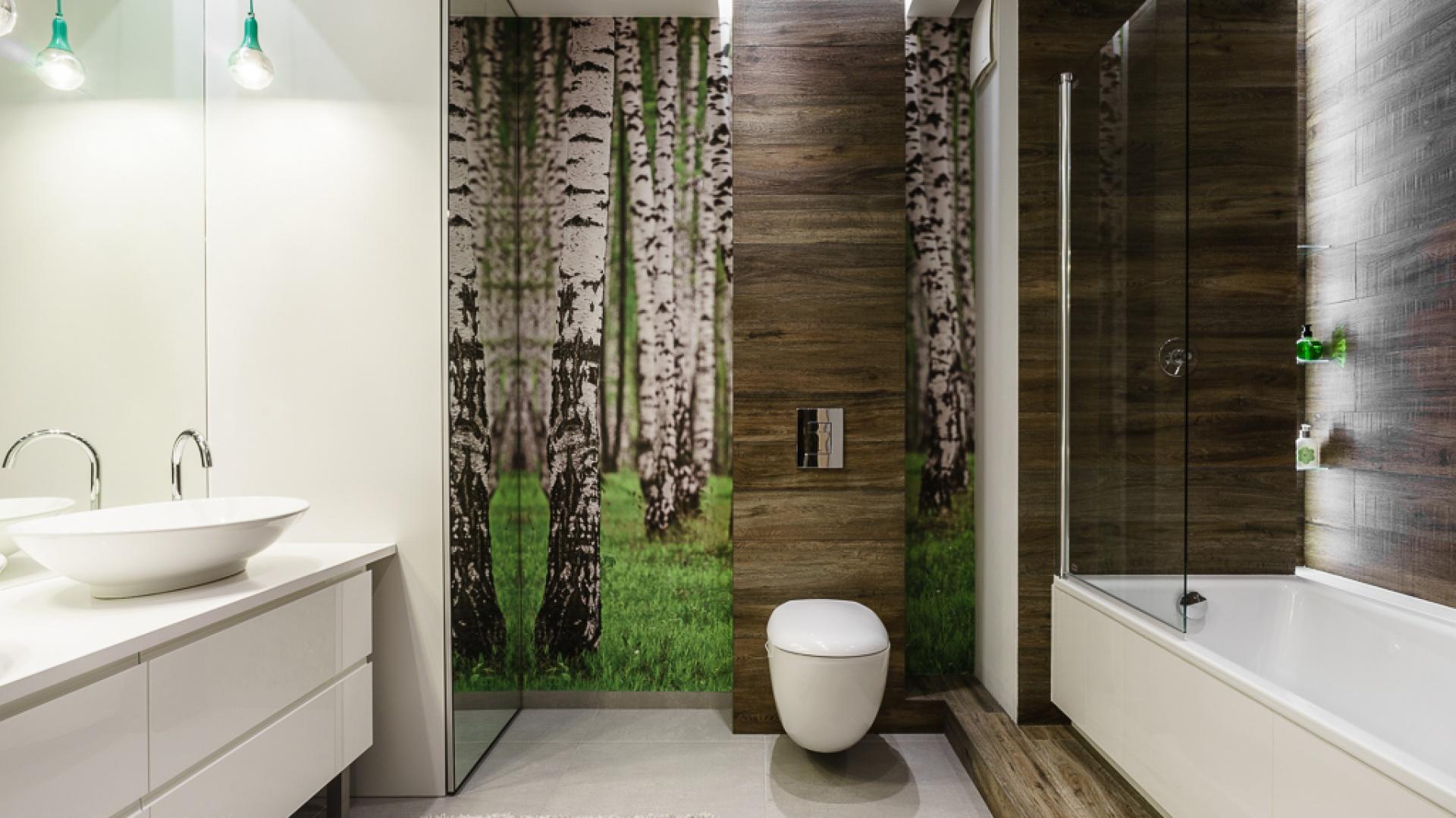 Obudowa stelaża wc pokryta drewnianą okleiną harmonizuje z leśną fototapetą. Projekt: Joanna Morkowska-Saj. Fot. Bartosz Jarosz