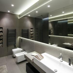 W minimalistycznej, szarej łazience duza role odgrywa światło, a także duże lustrzane powierzchnie. Projekt: Małgorzata Muc, Joanna Scott. Fot. Bartosz Jarosz