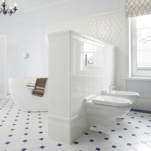 Biała łazienka urządzona w lekko klasycyzującym stylu. Biel przełamują niebieskie akcenty na podłodze. Projekt: Maciejka Peszyńska-Drews. Fot. Bartosz Jarosz