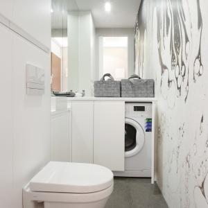 Niewielka łazienka za sprawą bieli, dużego lustra i praktycznych schowków zyskała przestrzeń w odbiorze wizualnym. Projekt: Karolina Łuczyńska. Fot. Bartosz Jarosz