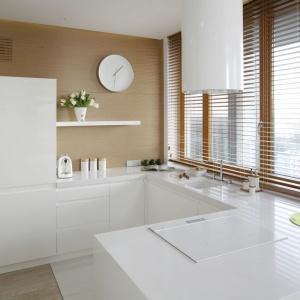 Minimalistyczna, biała zabudowa kuchenna stanęła na tle drewnianych płyt, którymi wykończono ścianę w kuchni. Projekt: Marcin Brzostek. Fot. Bartosz Jarosz