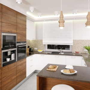 Wysoka zabudowa kuchenna znajdująca się na granicy kuchni ociepla wizualnie przeważająco białe pomieszczenie. Projekt: Agnieszka Hajdas-Obajtek. Fot. Bartosz Jarosz