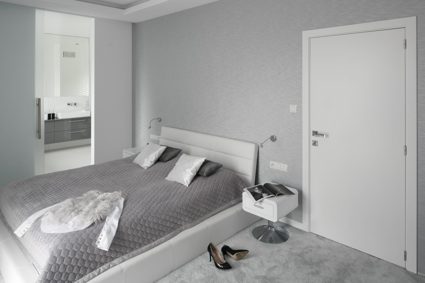 Puchata wykładzina, ściany oraz łóżko mają różne odcienie koloru szarego. Z aranżacją sypialni harmonizuje kolorystyka łazienki, z którą pomieszczenie jest połączone. Projekt: Katarzyna Mikulska-Sękalska. Fot. Bartosz Jarosz