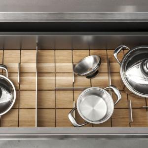 Oryginalne organizery do szuflad mają drewniane podstawy podzielone szachownicą  żłobień, w które wsuwać można różnej długości stalowe przegródki. Zapewniają pełną swobodę  kształtowania wewnętrznych podziałów i dopasowania ich do różnych wielkości i kształtów kuchennych przyborów. Fot. Zajc Kuchnie