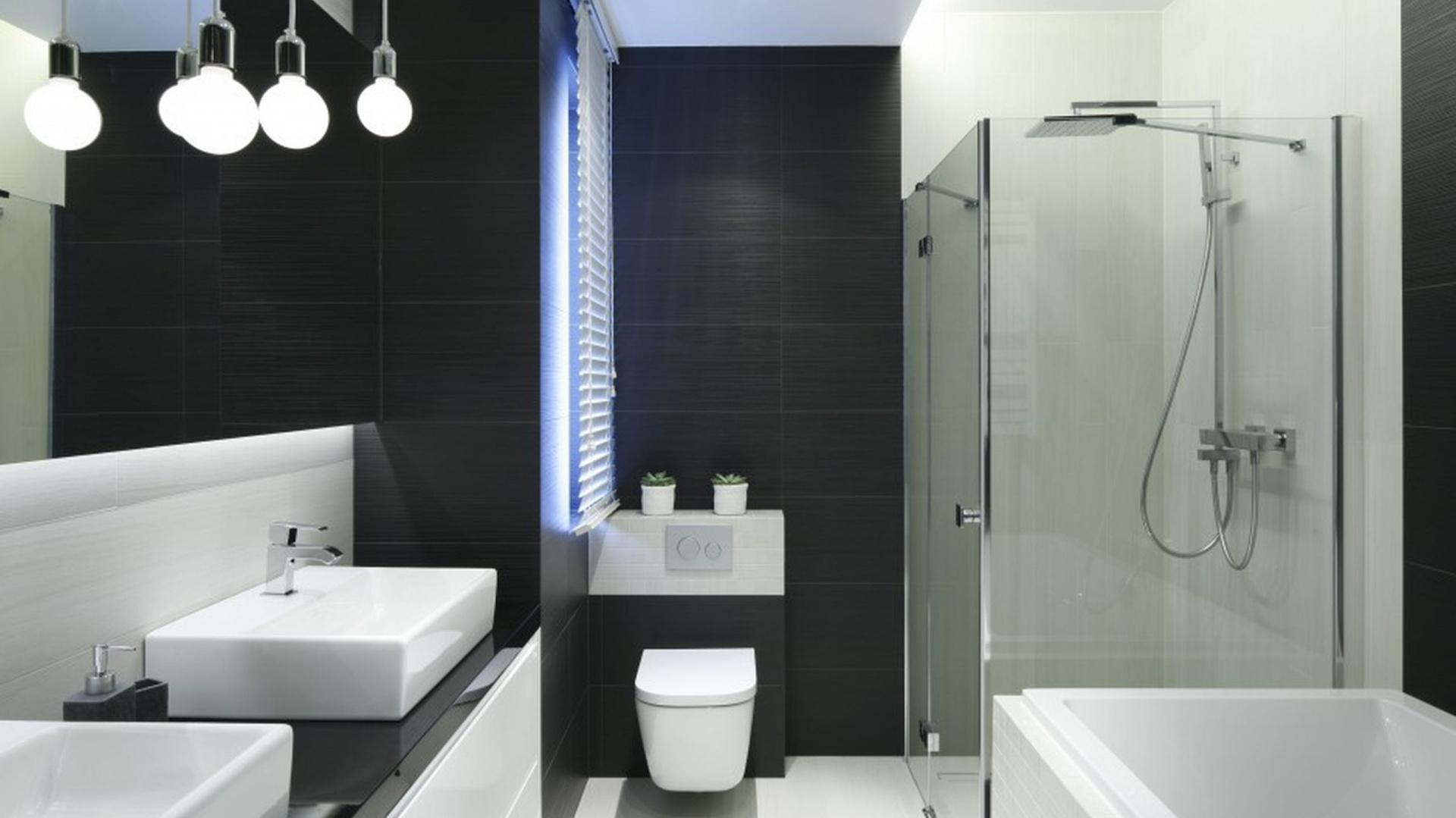 Biel i grafit, proste formy oraz odważne rozwiązania sprawiają, że łazienka jest elegancka i funkcjonalna, zachwyca lekką i nowoczesną aranżacją. Proj. Karolina Stanek-Szadujko, Łukasz Szadujko. Fot. Bartosz Jarosz