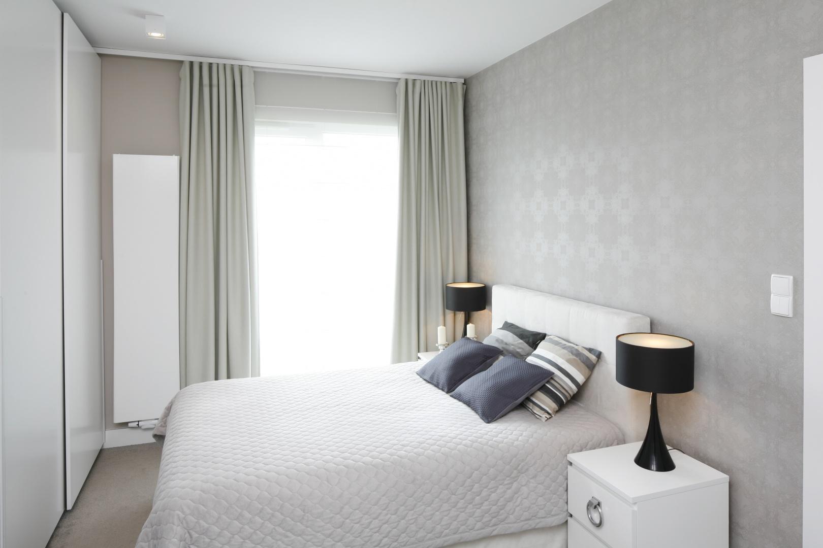 Zwiewne, szare zasłony oraz biel wizualnie studzą aranżację sypialni. Projekt: Małgorzata Galewska. Fot. Bartosz Jarosz
