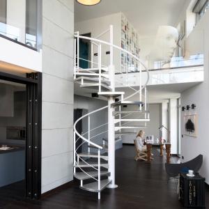 We wnętrzu urządzonym w klimacie soft loftu kręte metalowe schody pomalowane na biało są elementem przyciągającym wzrok. Projekt: Justyna Smolec. Fot. Bartosz Jarosz