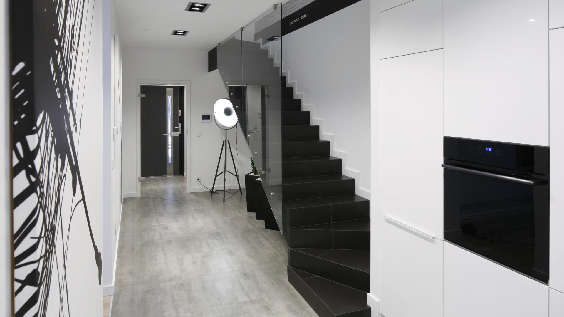 Eleganckie czarne stopnie, przesłonięte szklaną balustradą wychodzą bezpośrednio na kuchnię. Projekt: Karolina Stanek-Szadujko, Łukasz Szadujko. Fot. Bartosz Jarosz