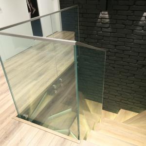Schody otulają tafle szkła i czarna cegła na ścianach. Projekt: Dominik Respondek. Fot. Bartosz Jarosz