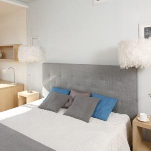 Sypialnię w bieli i szarościach ociepla dodatek drewna aranżacji, czyniąc wnętrze przytulnym. Projekt: Marta Kruk. Fot. Bartosz Jarosz